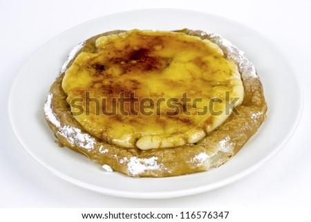 Typical ensaimada de Mallorca with a layer of burnt sugar and Catalan custard - stock photo