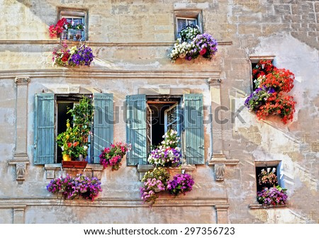 Typical facade of the old Provencal retro house with windows and wooden shutters decorated with colorful fresh flowers in Provence, Cote d'Azur, France - stock photo