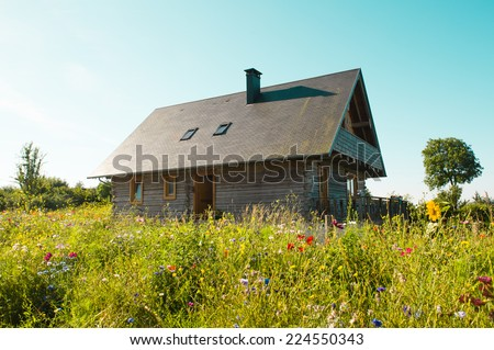 Typical farm in Normandy, France, in a green field with flowers - stock photo