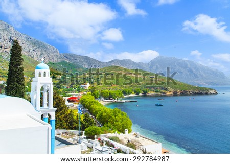 Typical Greek church with blue dome and sea bay in background, Greece - stock photo