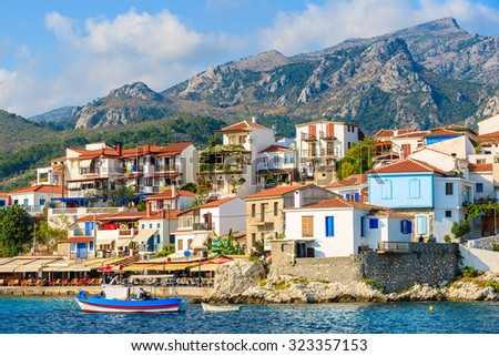 Typical Greek fishing boat in Kokkari bay with town houses in background, Samos island, Greece - stock photo
