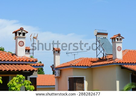 Typical Greek roofs with decorative chimneys and solar panel - stock photo