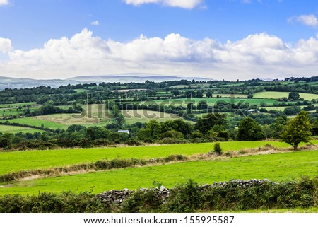 Typical green Irish country side with rolling fields and green patches - stock photo