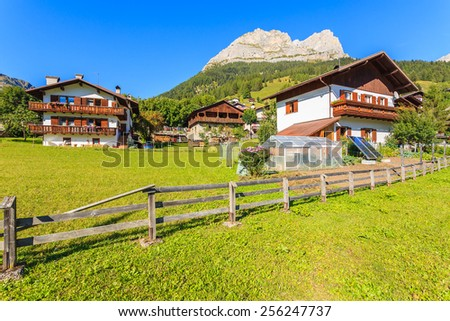 Typical houses in alpine village San Vito di Cadore in Dolomites Mountains on sunny summer day, Italy - stock photo