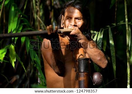 Typical huaorani hunter portrait, waorani reserve, Yasuni national park, Ecuador. Shoot in the jungle in ambient light. - stock photo