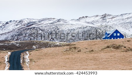 Typical Icelandic  landscape at  Reykjanes Peninsula with mountains covered in snow and empty asphalt road leading to a blue cottage house - stock photo