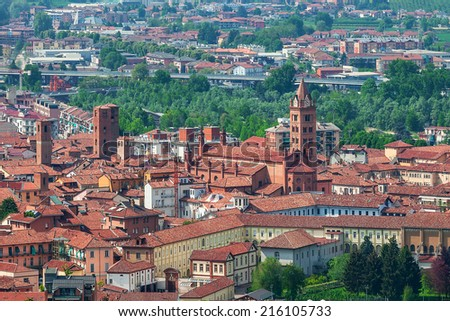 Typical italian houses with red rooftops and bell tower of the cathedral in old town of Alba, Italy. - stock photo