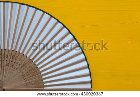 Typical Japanese hand fan made on the wooden yellow table - stock photo