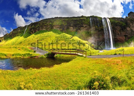 Typical landscape for the summer in Iceland. Across the stream near a waterfall Selyalandsfoss wooden bridge spanned - stock photo