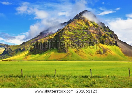 Typical landscape for the summer in Iceland. Bright green floral and farmland at the foot of steep mountains.  - stock photo