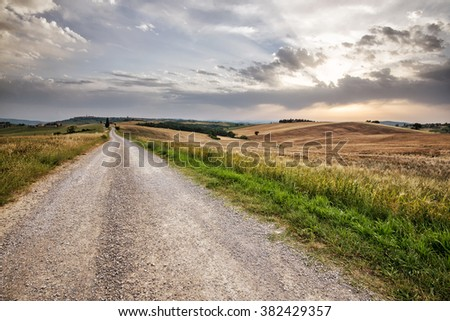 typical landscape in Tuscany in Val d'Orcia, fields, hills and trees under a clear sky - stock photo