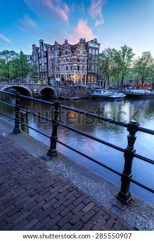 Typical late evening view of deep blue sky and canal houses behind a bridge in Haarlemmerbuurt district of Amsterdam, Netherlands - stock photo