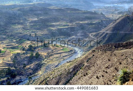 Typical mountain bird eye view  landscape. It is southern  American country -  Peru. Sacred Valley with the cultivated farmer fields is surrounded with high hills. On terraces poor farmers  grow corn. - stock photo