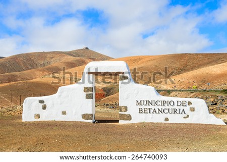 Typical municipality sign (white arch gate) near Betancuria village with desert mountain landscape in the background, Fuerteventura, Canary Islands, Spain - stock photo