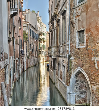 typical narrow canal with old colorful brick houses in Venice, Italy, Europe - stock photo