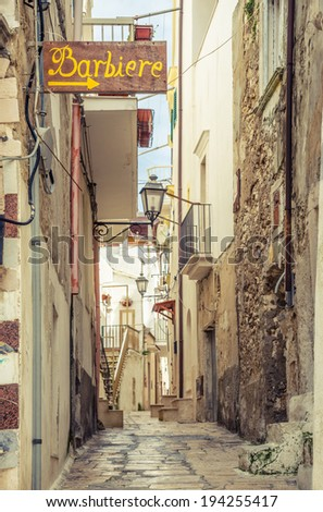 Typical narrow old street in Vieste, Apulia, Italy.Toned. - stock photo