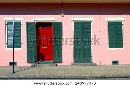Typical New Orleans French Quarter Style Architecture With Green Shutters on a Pastel Pink Color Painted Stucco Wall and a Red Door with Mail Slot. - stock photo