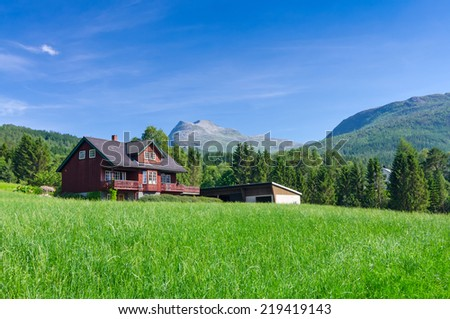 Typical Norwegian village house under the mountains - stock photo