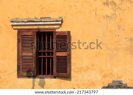 Typical old house with yellow wall, paper flower and wooden doors at Hoi An Ancient Town in early morning sunshine, Quang Nam, Vietnam. Hoi An is recognized as a World Heritage Site by UNESCO.  - stock photo