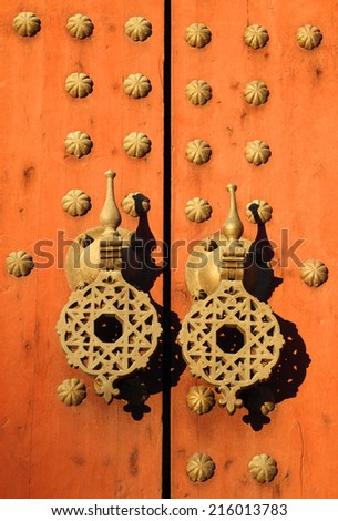 Typical old rustic studded wooden door with Islamic patterns on brass door-knock, Morocco. - stock photo