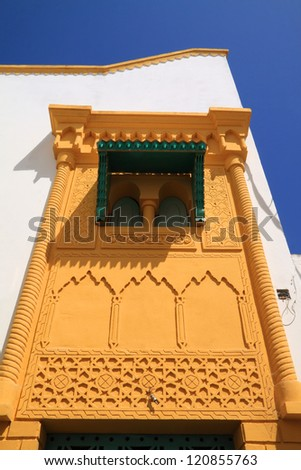 Typical, old, yellow intricately carved, Moroccan window and door-frame, against a deep blue sky, Azemmour, El Jadida, Morocco. - stock photo