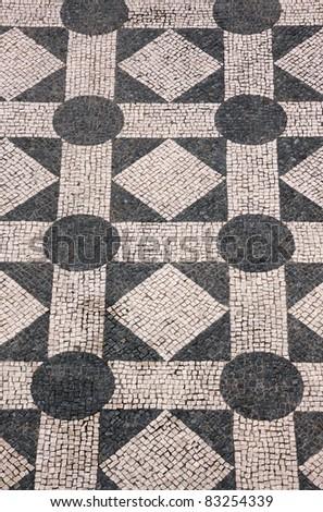 "Typical Portuguese black and white mosaic cobblestone  ""calcada""  pavement - Cascais Lisbon Portugal - stock photo"