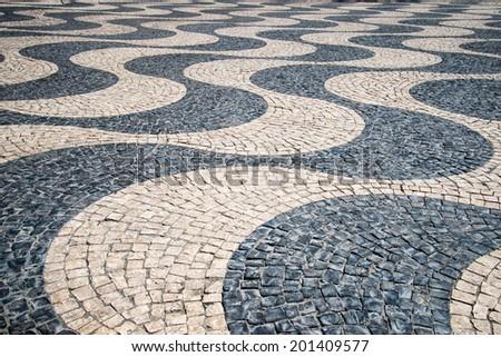 "Typical Portuguese ""calcada"" mosaic cobble stone paving, Lisbon, Portugal. - stock photo"