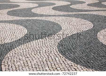 "Typical Portuguese  ""calcada"" mosaic  cobble stone paving,  Lisbon, Portugal. Also identical paving found in Copacabana and Ipanema in Rio de Janeiro, Brazil. - stock photo"