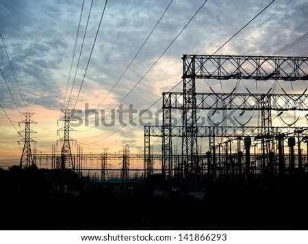 typical power lines, pylon and electrical substation - stock photo