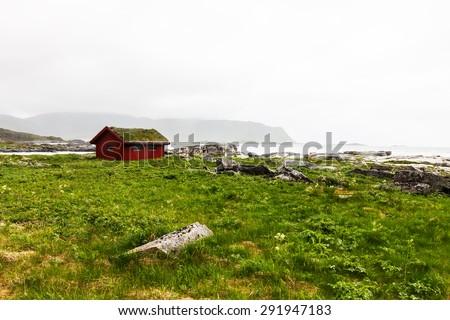 Typical red rorbu, fishing hut in village on Lofoten islands in Norway - stock photo