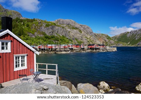 Typical red rorbu fishing huts in village of Nusfjord, unesco heritage on Lofoten islands, Norway - stock photo