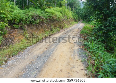 Typical rural gravel road in Sabah Malaysian Borneo. A road built across green foliage. - stock photo