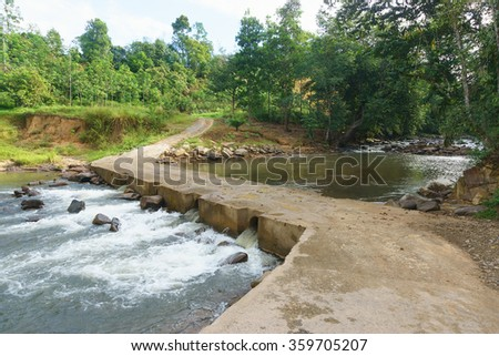 Typical rural road in Sabah Borneo with concrete river crossing using culvert.A part of road crossing river in the jungle of Sabah Malaysian Borneo. - stock photo