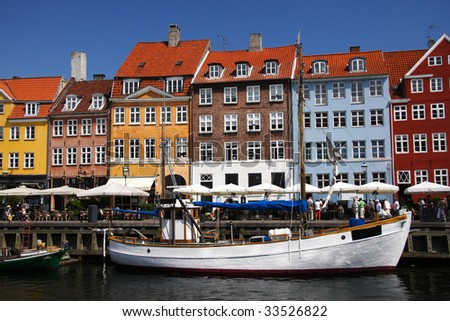 Typical scene from Copenhagen: Nyhavn harbor front and cafe's during summer. Denmark in summer. - stock photo
