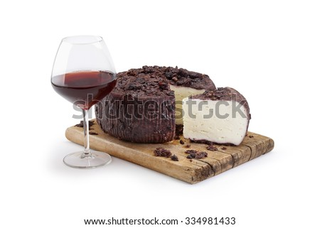 Typical Sicilian drunk cheese on a wooden cutting board with a wine glass on white background - stock photo