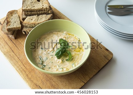 "Typical slovak spread made from sheep cheese called ""bryndza"", butter, yoghurt and herbs with baked breads.  Closeup on served food on white wooden table. - stock photo"
