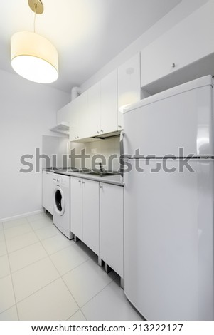 Typical small, white and compact kitchen interior design - stock photo