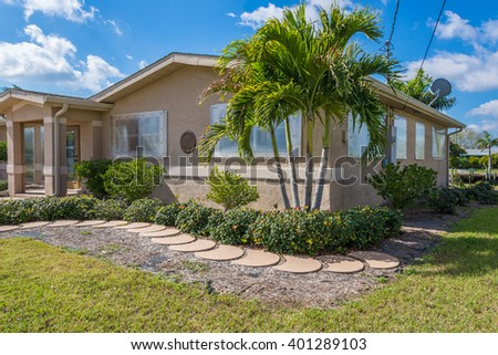 Typical Southwest Florida Concrete Block and Stucco Home.  Clear hurricane shutters on the windows and palm trees in the landscape. - stock photo