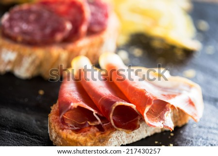 """Typical spanish appetizer called """"pinchos"""" with spanish ham and slice of bread. - stock photo"""