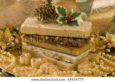Typical Spanish Christmas nougat in a golden plate - stock photo
