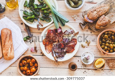 Typical spanish tapas concept. Concept include variety slices smoked cut dry sausages, ham, bowls with olives, small bbq peppers, bread baguette, veggies from above on wooden table. Rustic style. - stock photo