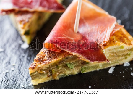 Typical spanish tapas: Tortilla de patatas with serrano ham. - stock photo