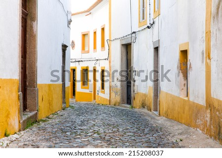 Typical street in the medieval city evora in Portugal, europe, with white houses and yellow bands, with medievel pavement and leading lines - stock photo