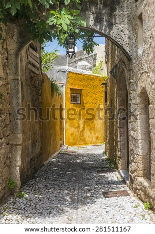 Typical street in the old town of Rhodes in Greece showing medieval type streets and architecture - stock photo