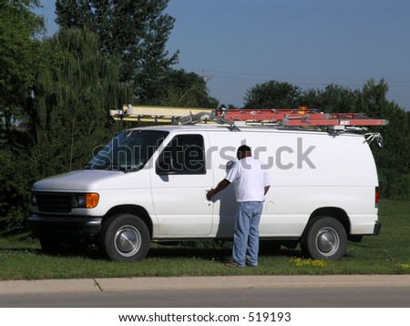 Typical tradesmans van with ladders on top - stock photo