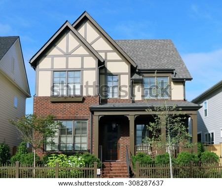 "Typical upper scale suburban home built in the ""Tudor"" style.  Homes are increasingly being built on smaller lots with garages facing the back of the property. - stock photo"