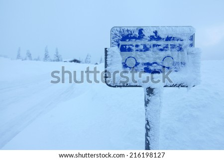 Typical view in Scandinavia at winter: hard snow covering a bus-stop sign after snowdrift in Norwegian highland  - stock photo