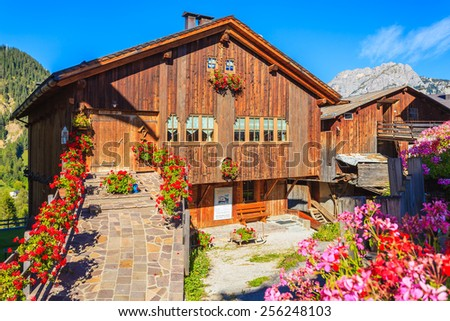 Typical wooden houses decorated with flowers in alpine village San Vito di Cadore in Dolomites Mountains on sunny summer day, Italy - stock photo