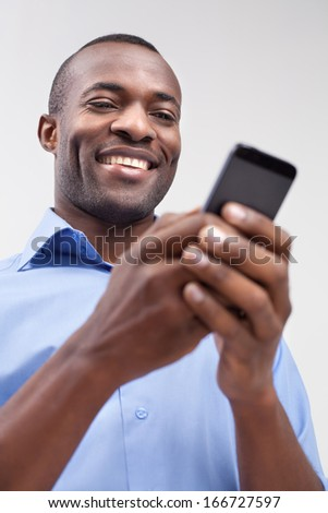 Typing a message. Low angle of cheerful black man typing something on the mobile phone and smiling while standing isolated on grey - stock photo
