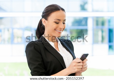 Typing business message. Beautiful young woman in formalwear holding mobile phone and looking at it with smile while standing outdoors - stock photo